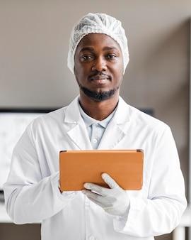 Ricercatore maschio di smiley nel laboratorio di biotecnologie con tablet