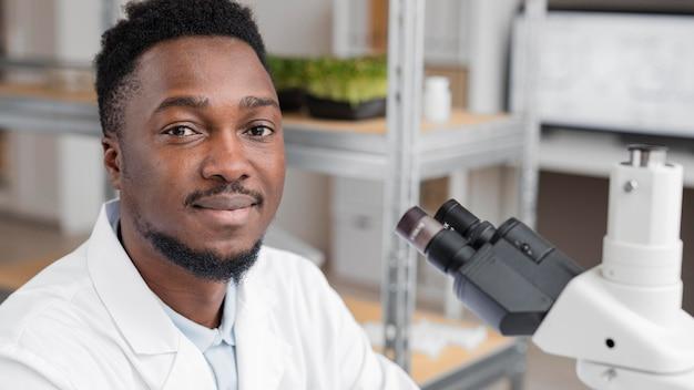 현미경을 사용하여 실험실에서 웃는 남성 연구원