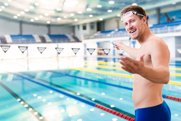 Smiley male swimmer inviting photographer to swim