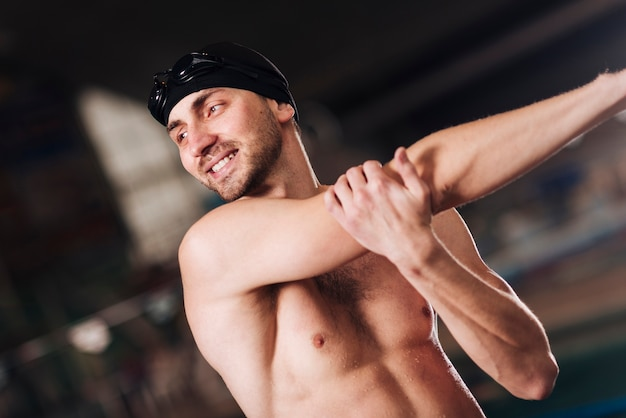 Smiley male swimmer stretching