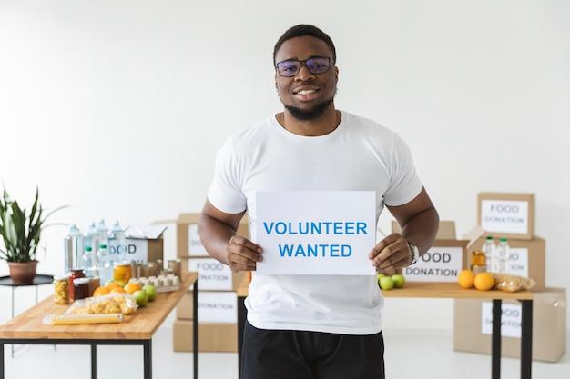 Смайлик-волонтер-мужчина держит чистый лист бумаги с информацией
