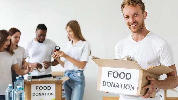 Смайлик-волонтер-мужчина держит коробку для пожертвований на еду