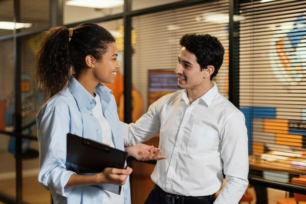 Смайлик мужчина и женщина вместе на рабочем месте разговаривают