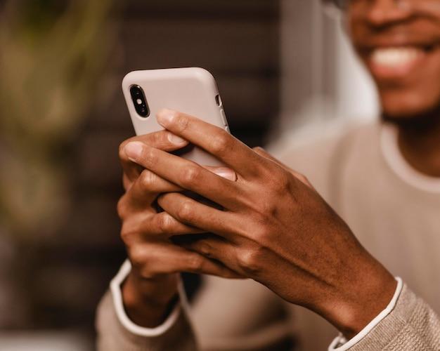 웃는 남자 집에서 스마트 폰을 사용하여