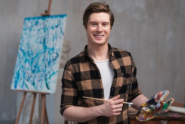 Uomo di smiley che mescola colori diversi per la sua pittura