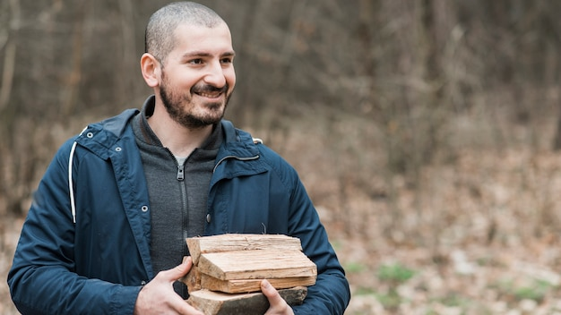 Smiley man carrying wood