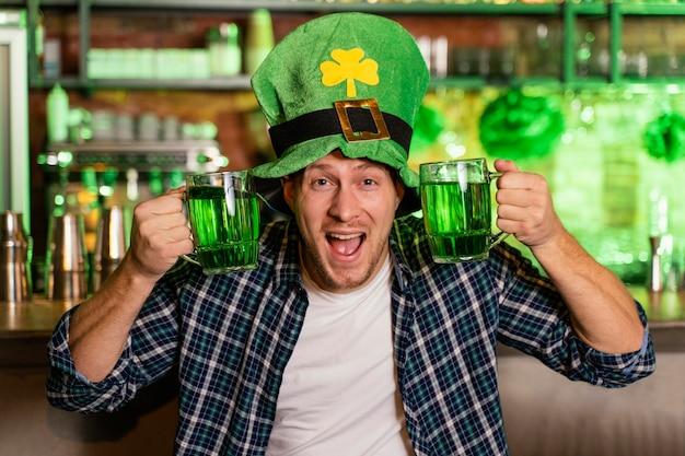 Uomo sorridente che celebra st. la giornata di patrick al bar