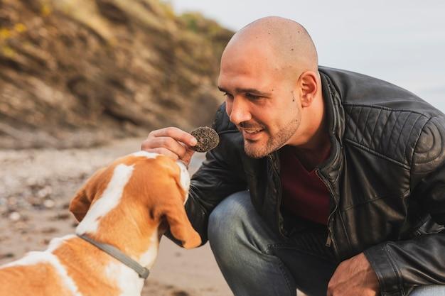 スマイリー男が犬に餌をやる