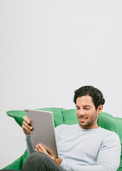 Smiley man having fun with the tablet