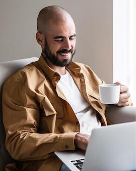 Смайлик мужчина держит чашку кофе