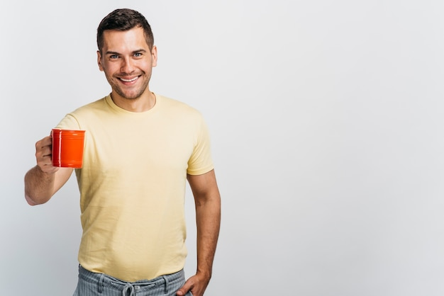 Smiley man holding a cup with copy space