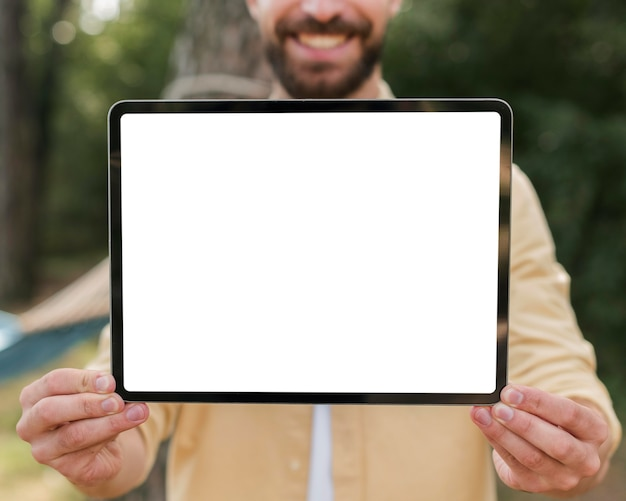 Smiley man holding up tablet while camping outdoors