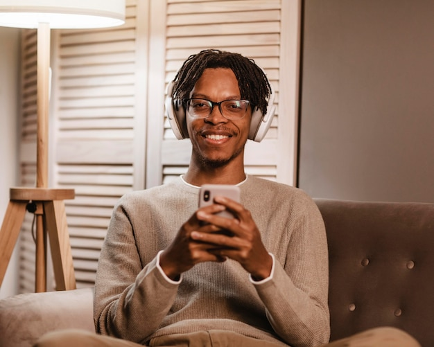 Uomo di smiley a casa sul divano utilizzando smartphone e cuffie