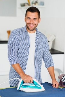 Smiley man at home ironing clothes