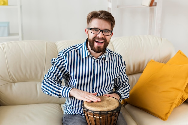 Smiley man at home with drum