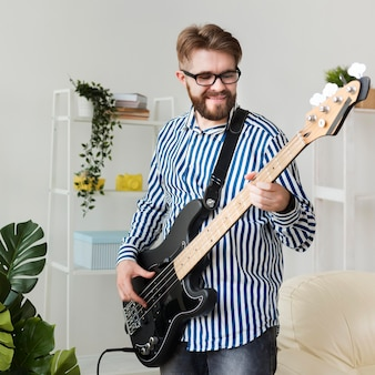 Smiley man at home with electric guitar