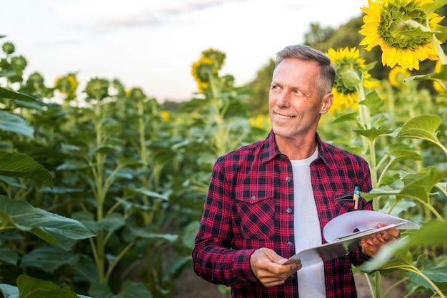 Uomo di smiley che osserva via su un campo