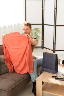 Smiley man looking at shirt