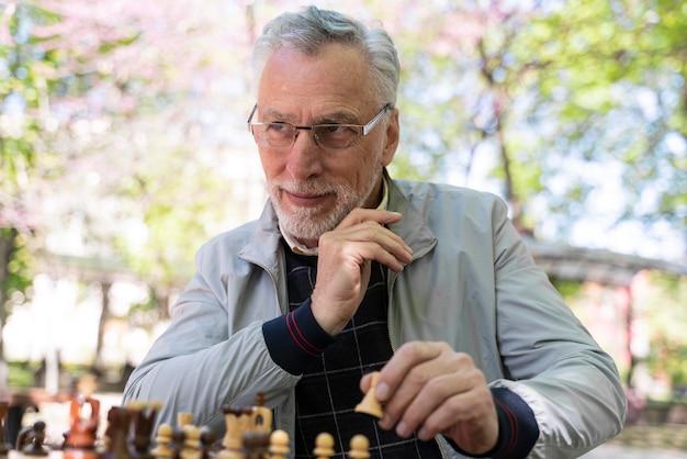 Uomo sorridente che gioca a scacchi colpo medio