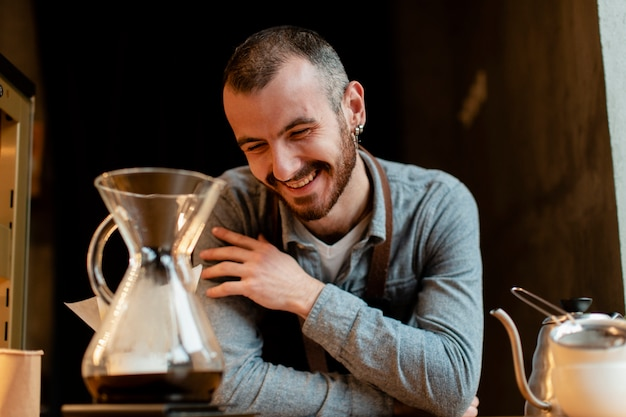 Smiley man posing in apron with coffee pot