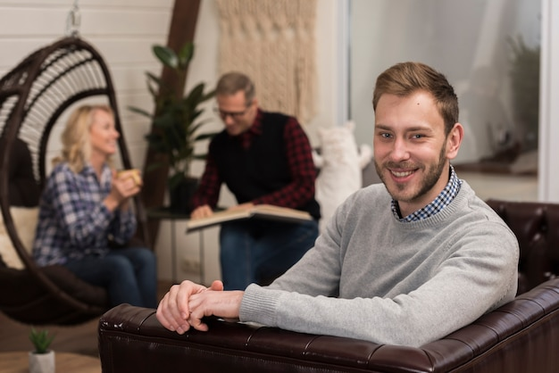 Smiley man posing on sofa with defocused parents