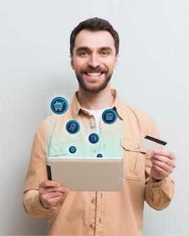 Uomo di smiley che compera online sul suo tablet