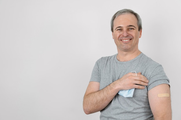 Smiley man showing bandage on arm after vaccination