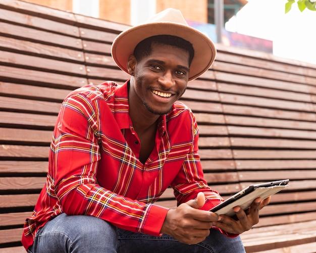 Uomo sorridente che si siede su una panchina e che tiene una tavoletta digitale