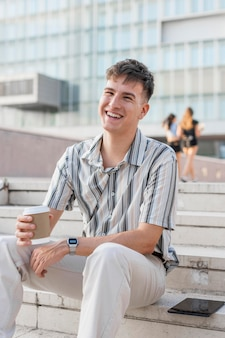 Smiley man sitting on steps outdoors while holding cup of coffee