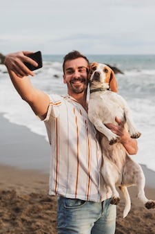Smiley man taking photo with dog