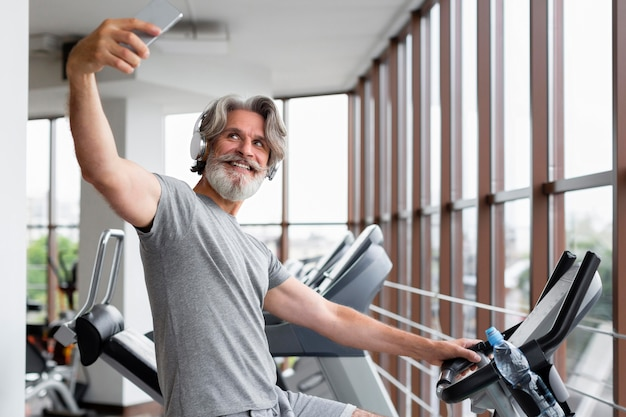 Smiley man taking selfies at gym