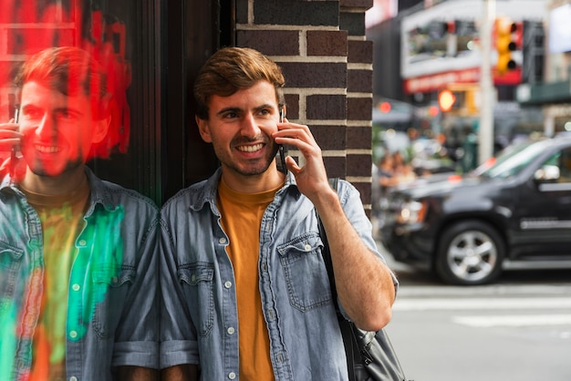 Smiley man talking at phone in city