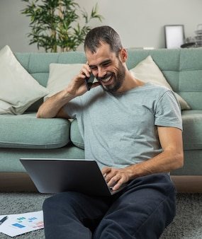 Smiley man talking on the phone at home while working on laptop