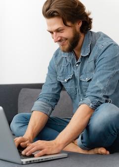 노트북의 키보드에 입력하는 웃는 남자