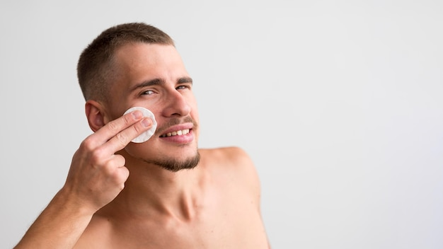 Smiley man using cotton pad on his face with copy space