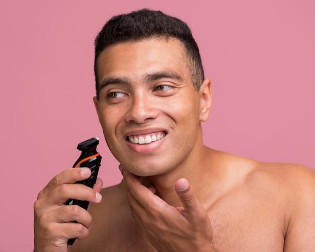 Uomo sorridente che utilizza un rasoio elettrico