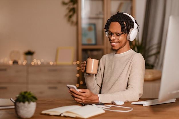 コーヒーを飲みながらスマートフォンを使用してスマイリー男