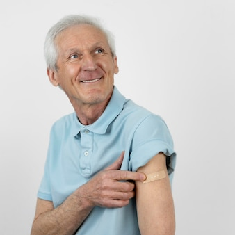 Smiley man with bandage on arm after vaccine shot
