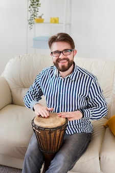 Smiley man with drum on sofa