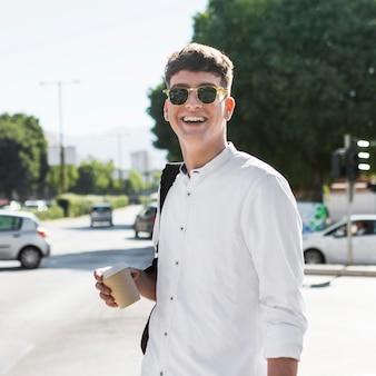 Uomo sorridente con gli occhiali da sole che bevono caffè all'aperto in città