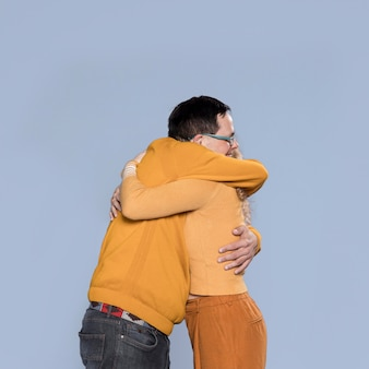 Smiley man and woman hugging