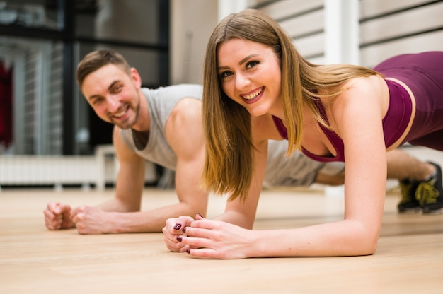 Smiley man and woman working out