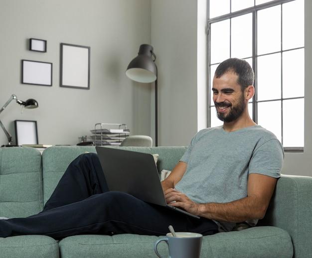 ラップトップで自宅で働くスマイリー男
