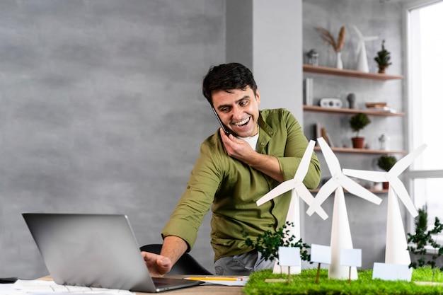 전화로 이야기하고 노트북을 사용하는 동안 친환경 풍력 발전 프로젝트에서 일하는 웃는 남자