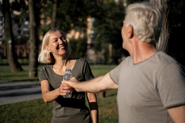 スマイリー成熟したカップルの屋外で水を飲む