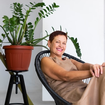 Smiley mature lady with plant behind