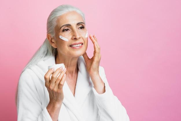Smiley mature woman applying skin care