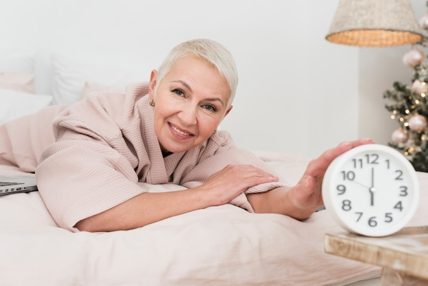 Smiley mature woman in bathrobe posing in bed with clock