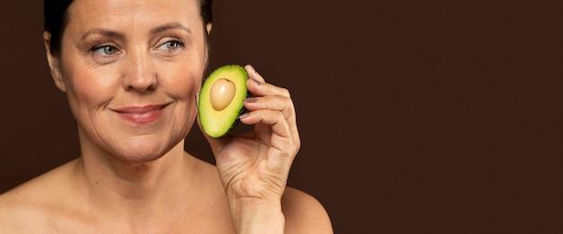Donna matura di smiley che tiene metà di un avocado con lo spazio della copia