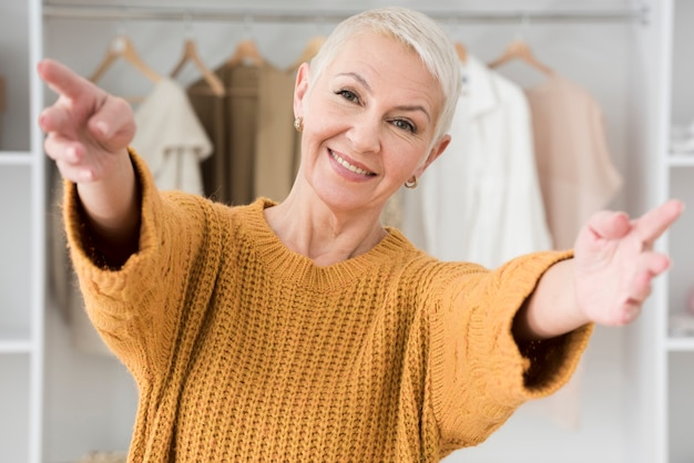 Smiley mature woman posing with open arms